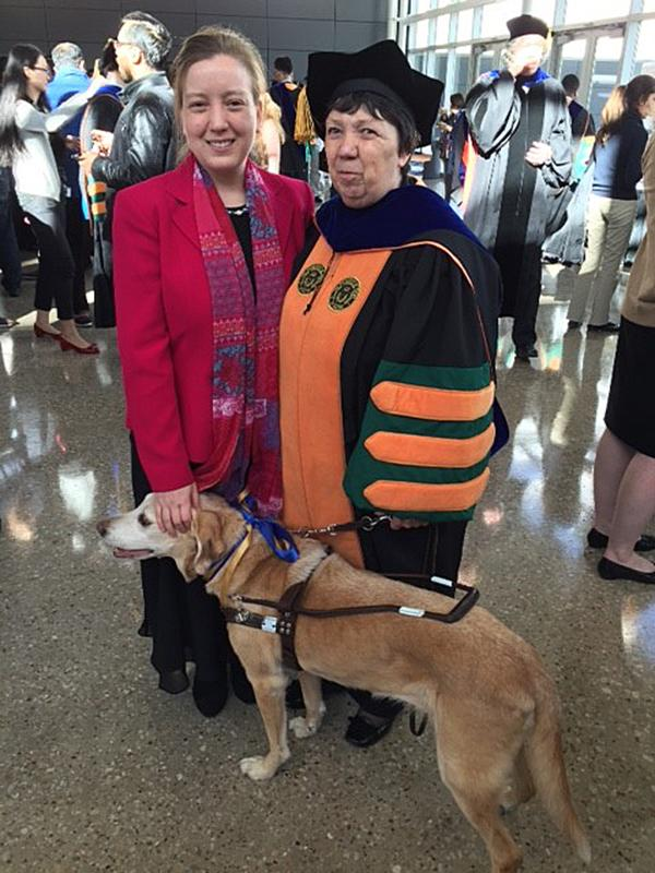 At UTD's doctoral graduation in December, Dr. Marilyn Bland poses with her daughter, Juliet Bond, and her guide dog, Honey. photo courtesy of Ruth Martin